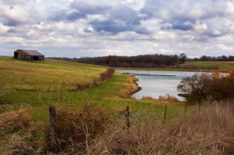 A farm with pond and a barn.