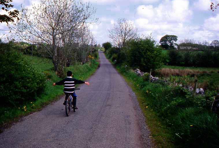 A boy riding a bicycle down a lane.